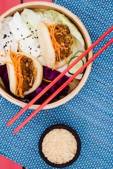 Reiskornschüssel mit gua bao und salat im bambusdampfer auf platzdeckchen