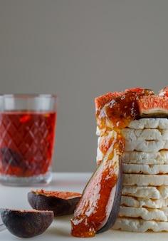 Reiskuchen mit feigen, marmelade, tasse tee nahaufnahme auf weiß und grau