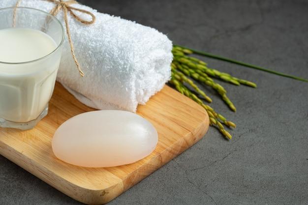 Reismilchseife, gerolltes handtuch, reispflanzen und ein glas milch auf holz probieren
