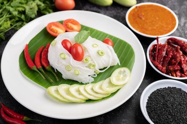 Reisnudeln in einem bananenblatt mit schön gelegtem gemüse und beilagen. thai essen.