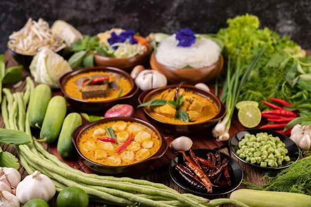 Reisnudeln in einer schüssel curry-paste mit chili, gurke, langbohne, limette, knoblauch und frühlingszwiebeln
