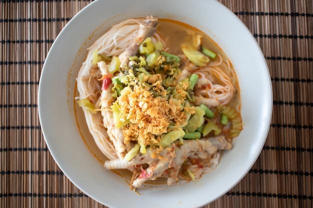 Reisnudeln in fischcurrysoße mit hühnerfüßen.
