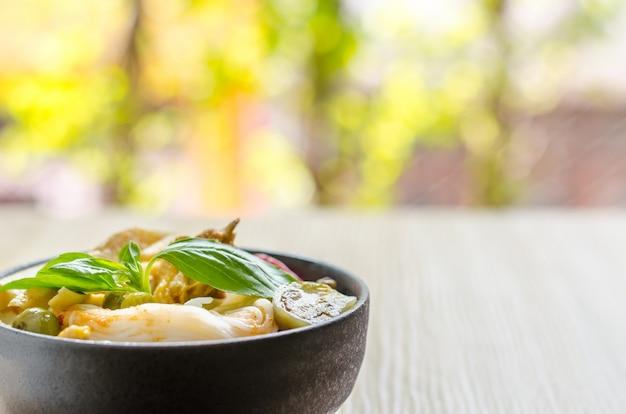 Reisnudeln in hühnercurrysoße mit gemüse auf hölzernem hintergrund