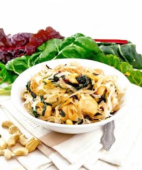 Reisnudeln mit blattrüben, hühnerbrust, cashewnüssen und sojasauce in einer schüssel auf küchentuch auf holzbretthintergrund