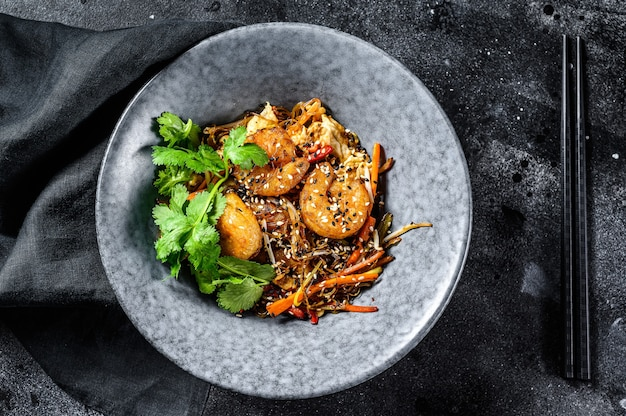 Reisnudeln mit garnelen und gemüse anbraten. asien wok