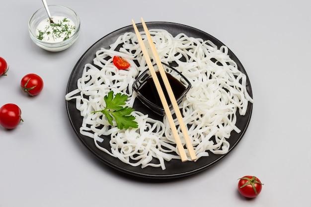 Reisnudeln mit sauce, bambusstangen auf schwarzem teller. kirschtomaten in schüssel mit weißer soße auf tisch. grauer hintergrund. draufsicht.