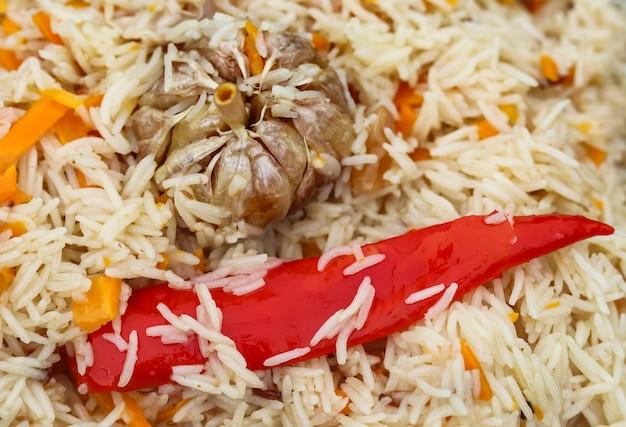 Reispilaf in einem großen gusseisentopf auf feuer kochen