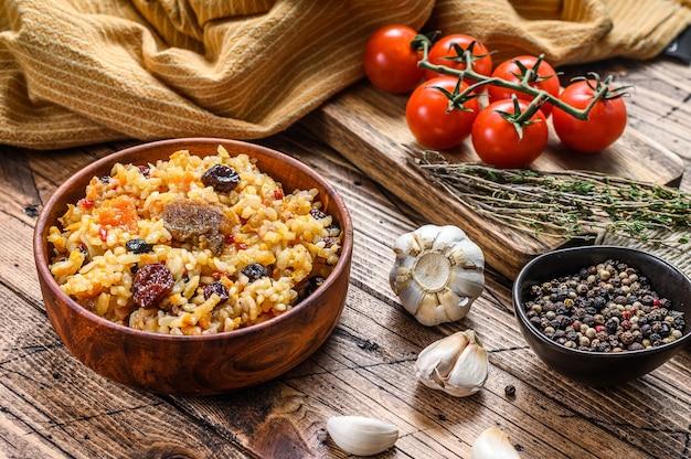 Reispilaf mit lammfleisch und gemüse in einer holzschale