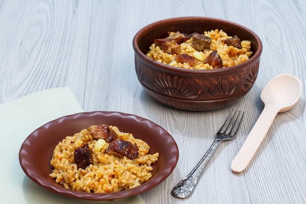 Reispilaw auf tonplatte und schüssel mit fleisch und gemüse. holzlöffel und metallgabel neben dem geschirr