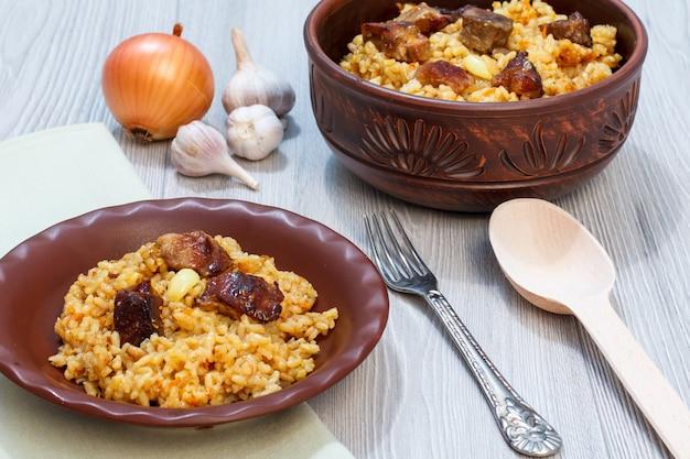 Reispilaw auf tonplatte und schüssel mit fleisch und gemüse - zwiebel, knoblauch, paprika, paprika. holzlöffel und metallgabel neben dem geschirr