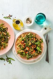 Reissalat mit gebackenen paprika, rucola, oliven und kapern. gesundes veganes frühlingsrezept für die ganze familie oder party