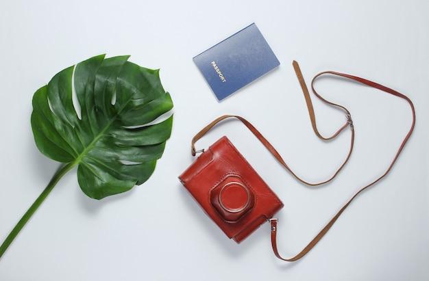 Reiste minimalistisches stillleben. monstera-blatt, retro-kamera im umschlag, pass auf weißem hintergrund. draufsicht