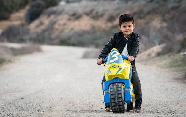 Reiten des kleinen jungen auf motorradspielzeug