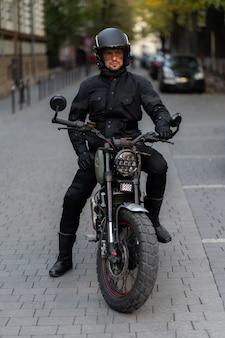 Reiter mann mit bart und schnurrbart in schwarzer sonnenbrille und korrekter bikerjacke sitzen bei sonnenuntergang auf klassischem rennmotorrad. brutaler spaß urbaner lebensstil.