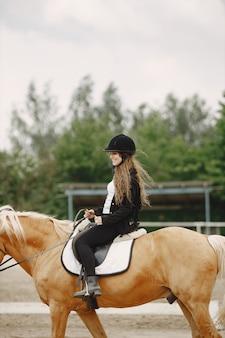 Reiterfrau, die ihr pferd auf einer ranch reitet. frau hat langes haar und schwarze kleidung. reiterin auf ihrem braunen pferd.