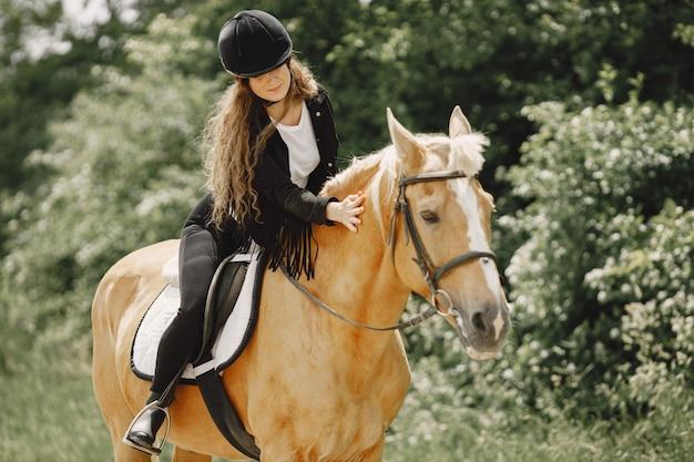 Reiterfrau, die ihr pferd auf einer ranch reitet. frau hat langes haar und schwarze kleidung. reiterin, die ihr braunes pferd berührt.