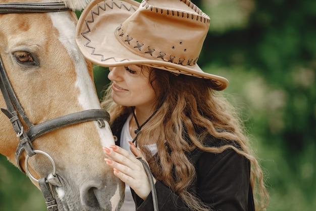 Reiterfrau, die mit ihrem pferd auf einer ranch spricht frau hat langes haar und schwarze kleidung. weiblicher reiter, der ein pferd berührt