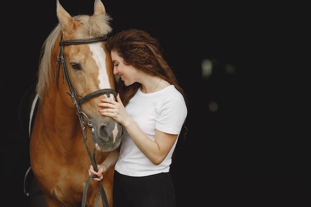 Reiterfrau, die mit ihrem pferd in einem stall spricht frau hat langes haar und weißes t-shirt. hintergrund ist dunkel und schwarz.
