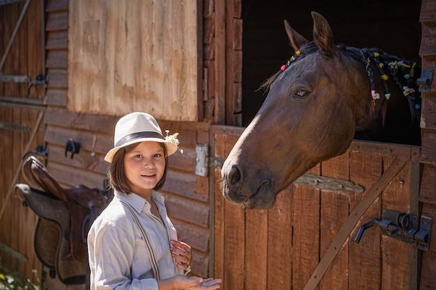 Reiterin des kleinen mädchens kommuniziert mit pferd nach pferdesport. braune stute späht freundlich aus dem stall. tierthemen.