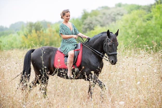 Reitmädchen gehen mit ihrem schwarzen pferd