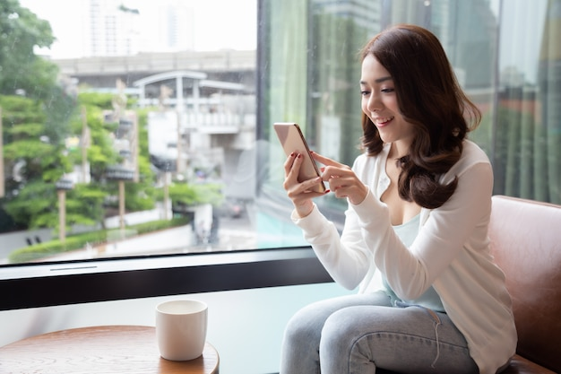 Reizend asiatinlächeln, das gute nachrichten am handy während des restes in der kaffeestube liest