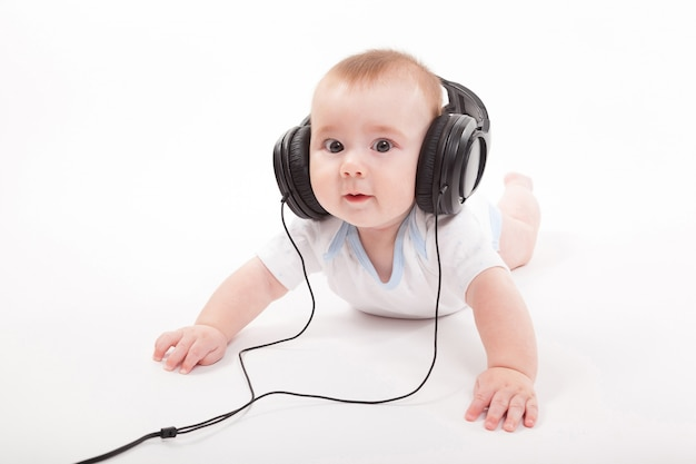 Reizend baby auf einem weißen hintergrund mit kopfhörern hörend auf
