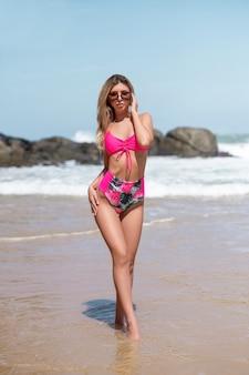 Reizend blondine, die in einem rosa badeanzug mit wassermelonen in den gläsern auf der küste steht im sandwasser aufwirft