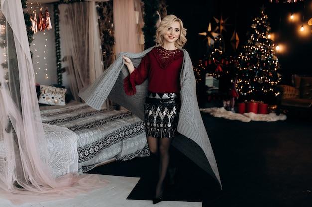 Reizend blondine umhüllt sich im grauen plaid, das auf einem bett vor einem weihnachtsbaum sitzt