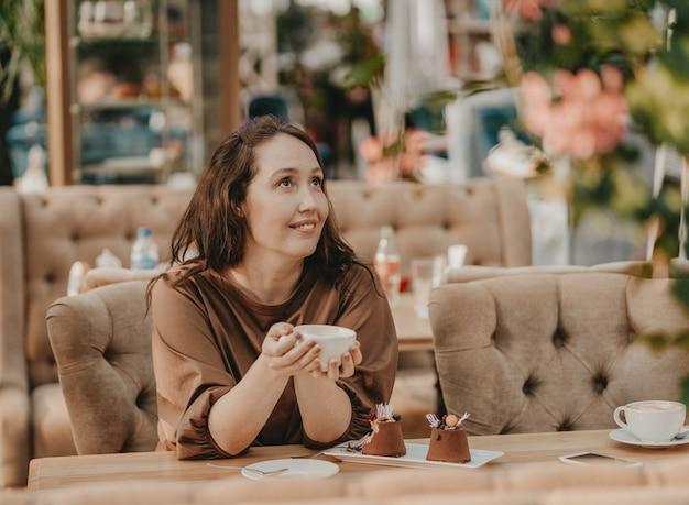 Reizend brunettefrau mit dem langen gelockten haar, das am fenster im café mit tasse kaffee in den händen und im nachtisch auf tabelle sitzt