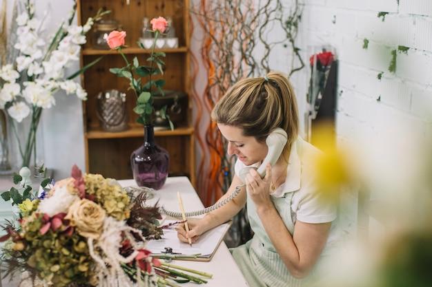 Reizend florist, der anmerkungen während des telefongesprächs macht