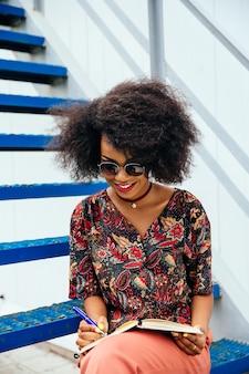 Reizend junge afroamerikanerfrau in der sonnenbrille, die auf treppen mit lehrbuch sitzt