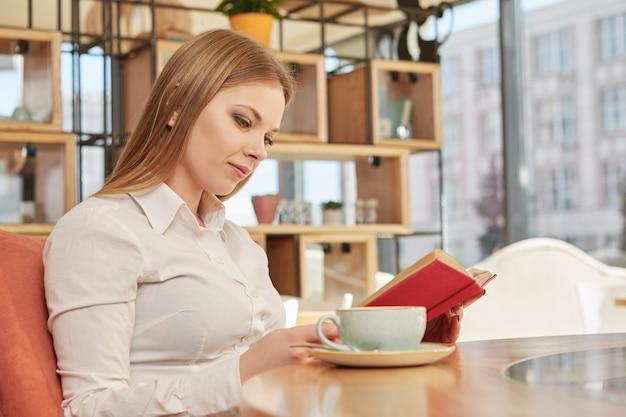 Reizend junge busnesswoman, die ein buch, entspannend an der kaffeestube liest
