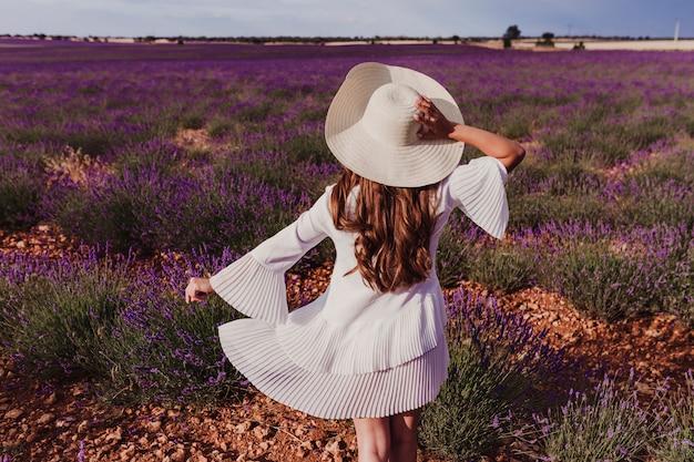 Reizend junge frau mit einem hut und einem weißen kleid auf einem purpurroten lavendelgebiet bei sonnenuntergang. lifestyle im freien. rückansicht