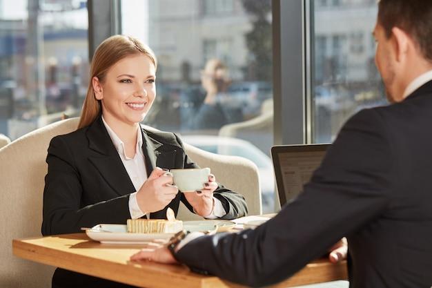 Reizend junge geschäftsfrau, die kaffee auf einer sitzung mit kollegen genießt