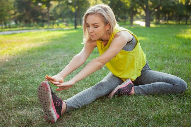Reizend junge sportlerin, die morgens am park trainiert