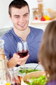 Reizend junger mann, der mit seiner freundin zu abend isst