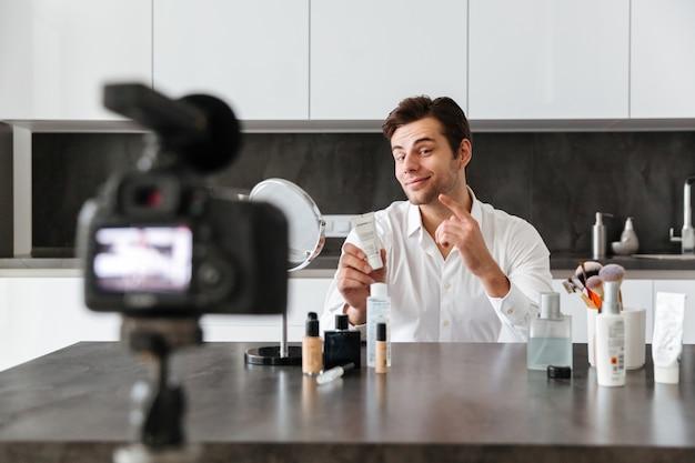 Reizend junger mann, der seine videoblogepisode filmt