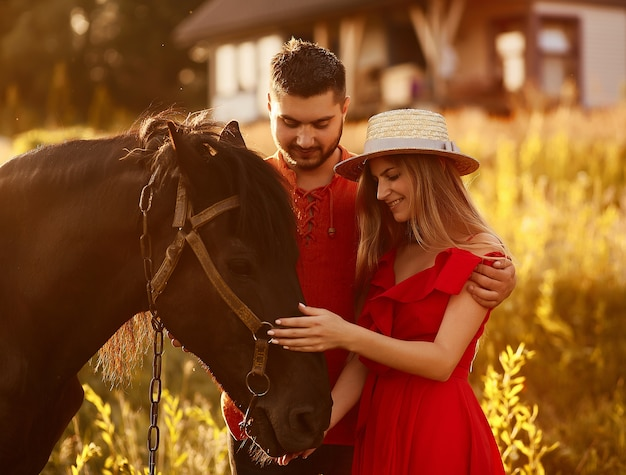 Reizend junges paar steht mit einem braunen pferd vor einem landhaus