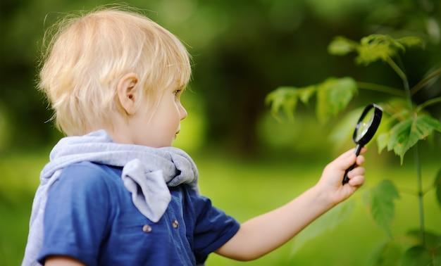 Reizend kind, das natur mit lupe erforscht