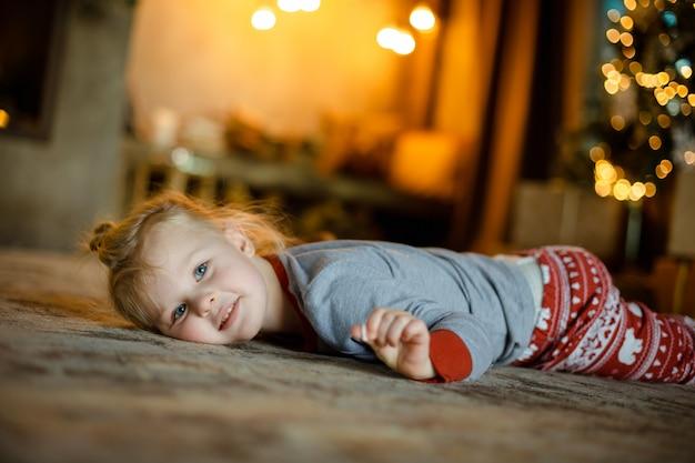 Reizend kleine blondine auf dem teppich auf dem hintergrund eines verzierten weihnachtsbaums und der brennenden girlanden. gemütliche weihnachten