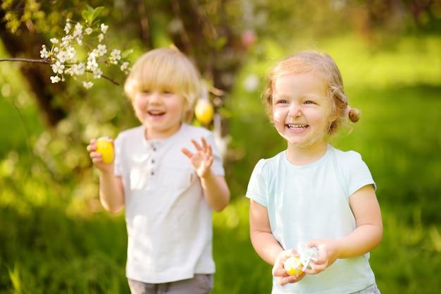 Reizend kleine kinder, die im frühjahr am ostertag nach gemaltem park der eier jagen.