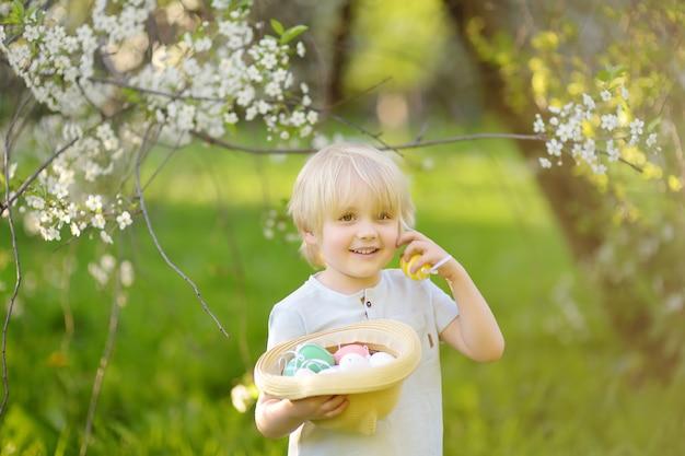 Reizend kleiner junge, der im frühjahr für park ostereies am ostertag jagt