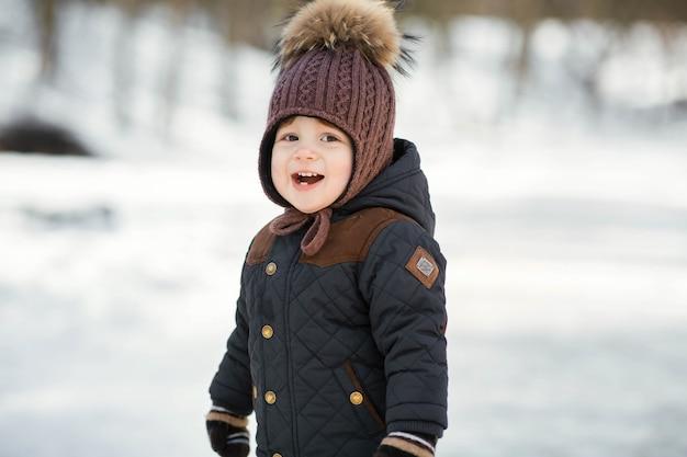 Reizend kleiner junge in einem lustigen winterhut wirft im park auf