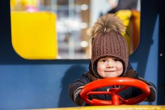 Reizend kleiner Junge spielt im Spielzeugauto draußen