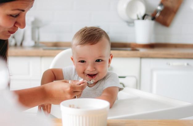 Reizend kleines baby, das ersten lebensmittelbrei mit löffel an der küche isst.