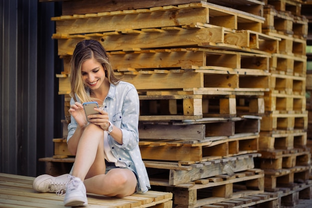 Reizend mädchen, das auf einer palette unter verwendung des intelligenten telefons sitzt