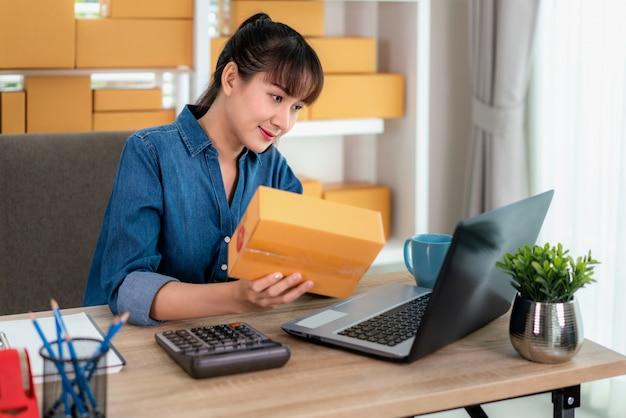 Reizend schöne asiatische jugendlichinhaber-geschäftsfrau arbeiten zu hause für das on-line-einkaufen und überprüfen detail im briefkasten mit laptop mit büroeinrichtung, unternehmerlebensstilkonzept