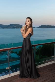 Reizend schönes mädchen, das in der hand in einem schokoladenabendkleid mit einem glas champagner aufwirft