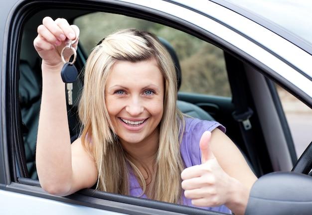 Reizend weiblicher fahrer, der einen schlüssel zeigt, nachdem er ein neues auto bying gemacht hat