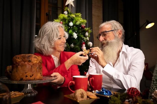 Reizende ältere paare, die weihnachtsplätzchen essen